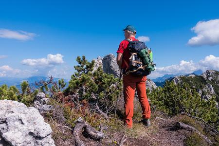 Hiker admire the mountain panorama of the peak