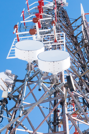 Telecommunication network repeaters, base transceiver station. Tower wireless communication antenna transmitter and repeater. Telecommunication tower with antennas. Cell phone telecommunication tower