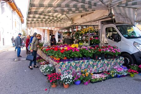 Udine, Italy - April 2 2019 :People at the local traditional outdoor market. Stall for the sale of garden flowers.