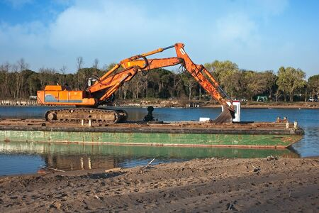 Excavator for channel dredge on a barge.