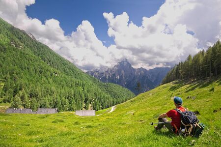 Hiker sitting on the lawn admires the view. Alps Italy