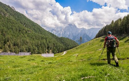 Hiker walk on trail and admiring the panorama. Italy Alps. Standard-Bild