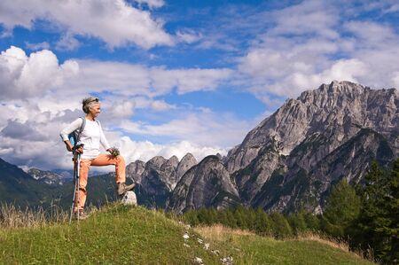Frau Wanderer Wandern mit Blick auf die malerische Aussicht auf die Berglandschaft. Abenteuerreisen im Freien Person, die sich während der Naturwanderung entspannt