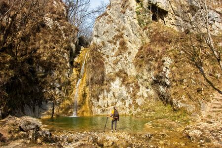Female hiker arrives and admires a waterfall with a beautiful puddle of water Standard-Bild