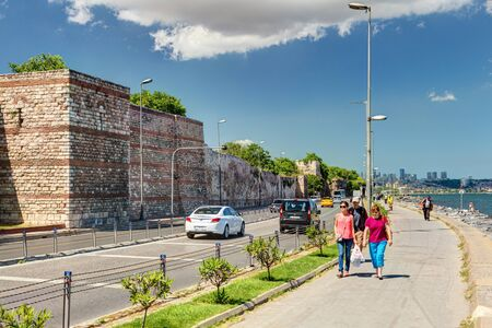 constantinople ancient: People walk along the promenade past the ancient sea walls of Constantinople on May 27, 2013 in Istanbul, Turkey  In ancient Constantinople had the most powerful fortifications in the world  Editorial