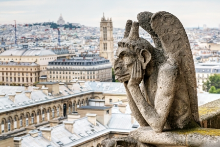 Chimera (gargoyle) of the Cathedral of Notre Dame de Paris overlooking Paris, France Stock Photo