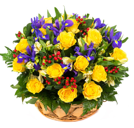 Natural yellow roses and blue irises in a basket isolated on white