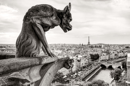 Chimera  gargoyle  of the Cathedral of Notre Dame de Paris overlooking the Eiffel Tower in Paris, France 免版税图像