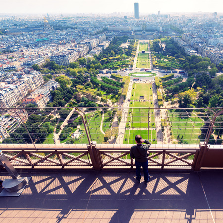 Tourist looking to the Champ de Mars on the observation deck of the Eiffel Tower in Paris  The Eiffel tower is one of the major tourist attractions of France