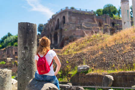 Young female tourist rests on the ruins of the Roman Forum in Rome, Italy photo