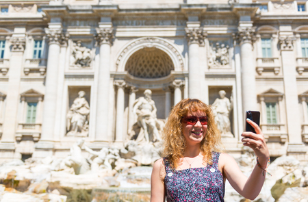 Selfie of a young female tourist on the background of the\ Trevi Fountain in Rome, Italy