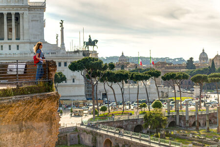 Young female tourist looks at the Forum of Trajan and the Piazza Venezia in Rome, Italy photo