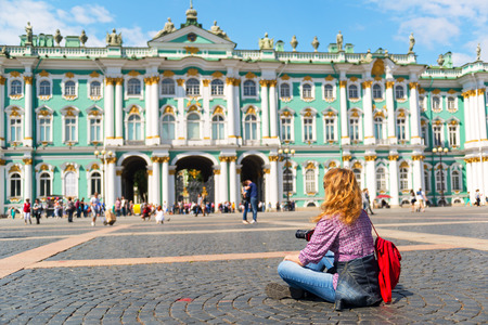 Young female tourist resting on the square in front of the Winter Palace in St. Petersburg, Russia