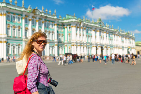 Pretty female tourist passes the Winter Palace in Saint Petersburg, Russia photo