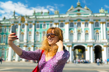 Selfie of a young female tourist on the background of the Winter Palace in Saint Petersburg, Russia 免版税图像