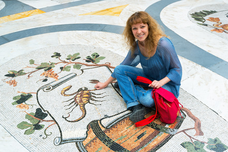 Young female tourist sitting on the image of the Zodiac sign Scorpio in Galleria Umberto I in Naples, Italy photo