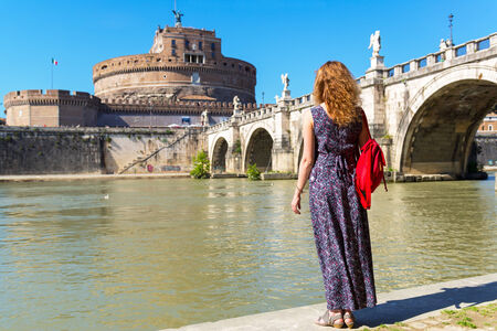 Young female tourist looks at the Castel Sant`Angelo in Rome, Italy photo