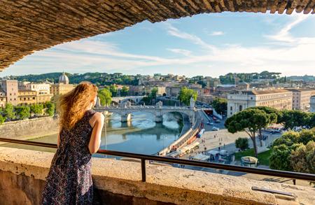 Jonge vrouwelijke toerist die de mening van Rome van de Castel Sant `Angelo, Italië bewonderen