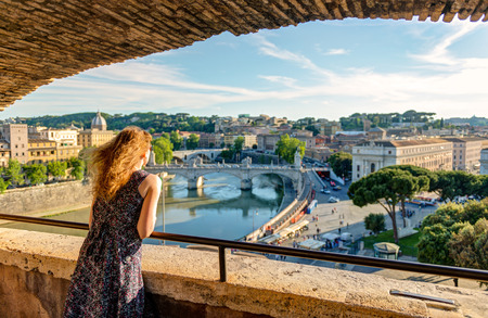 tourist site: Young female tourist admiring the view of Rome from the Castel Sant`Angelo, Italy