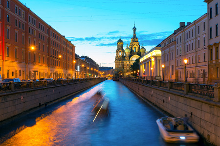 Tourist boats sail to the Church of Savior on Spilled Blood at White Night in Saint Petersburg, Russia. This is an architectural landmark of central St Petersburg, and a unique monument to Alexander II. Stock Photo