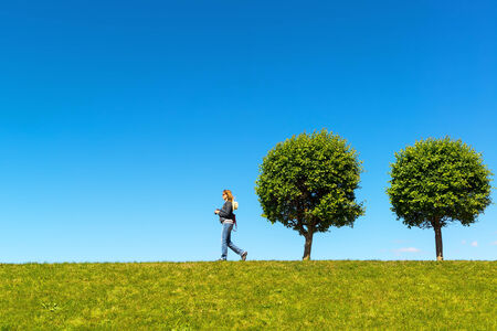 Young woman walking on the beautiful hill in summer day photo
