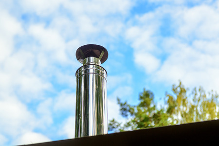 Modern chimney on the roof of house