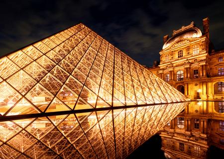 PARIS - 25 septembre 2013: Le célèbre pyramide de verre du Louvre. Le Louvre est l'un des plus grands musées du monde et l'une des principales attractions touristiques de Paris.