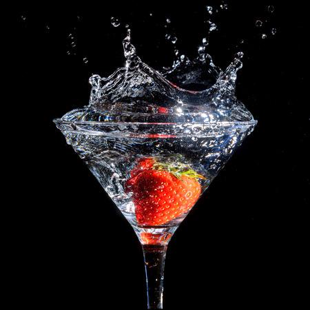 Strawberry splashing into glass of martini on a black background