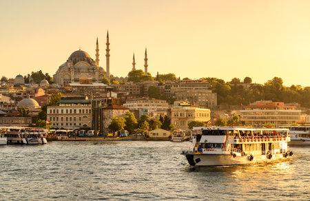 Toeristische boot zeilen op de Gouden Hoorn in Istanbul bij zonsondergang, Turkije Redactioneel
