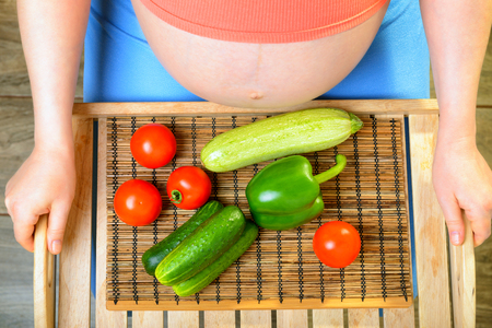 Pregnant woman with vegetables photo