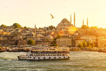 Toeristische boot drijft op de Gouden Hoorn in Istanbul bij zonsondergang, Turkije Redactioneel