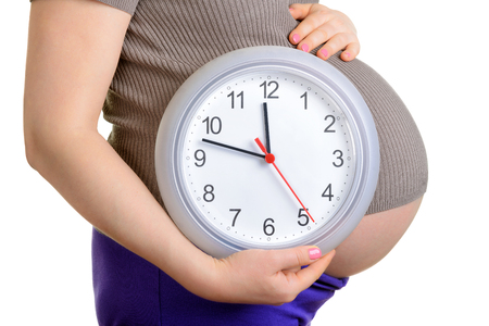Pregnant woman holding wall clock. Its time. Isolated on white. photo