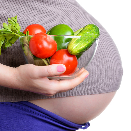 Pregnant woman holding a fresh vegetables, isolated on white background photo