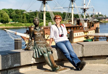 recognised: VELIKY NOVGOROD, RUSSIA - JUNE 12, 2014: Female tourist posing next to the sculpture The girl on the bridge. UNESCO recognised Veliky Novgorod (Novgorod the Great) as a World Heritage Site in 1992.