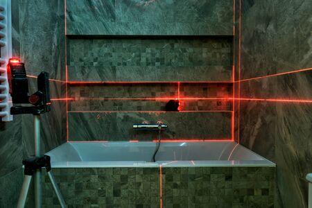 Laser measurement during bathroom renovation. Construction tools and equipment. 免版税图像