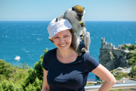 alupka: Young woman posing with a monkey on a resort on the Black Sea in Crimea. The famous Castle Swallows Nest in the distance. Crimea is a popular holiday destination in Russia. Stock Photo