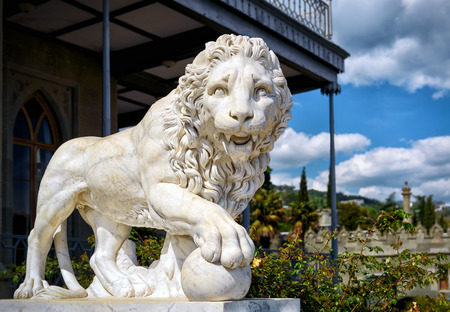 ALUPKA, RUSSIA - MAY 20, 2016: Statue of lion at the Vorontsov Palace facade in the town of Alupka, Crimea. This palace is a tourist attraction of the Crimea.
