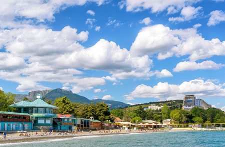 a bathing place: ALUSHTA, RUSSIA - MAY 15, 2016: Tourists sunbathe and swim at the beach. Alushta is a well-known resort in the Crimea.