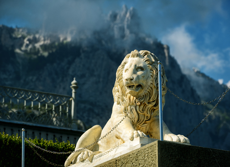 ALUPKA, RUSSIA - MAY 20, 2016: Statue of lion at the Vorontsov Palace on the background of Ai-Petri mountain, Crimea. This palace is a tourist attraction of the Crimea.