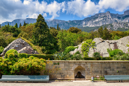 vorontsov: ALUPKA, CRIMEA - MAY 20, 2016: The garden at the Vorontsov Palace. Mountain Ai-Petri in the distance. This palace is one of the attractions of Crimea.
