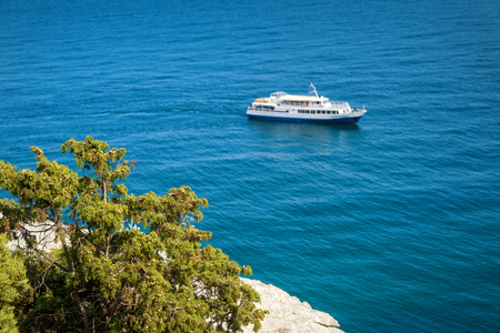 The Black Sea coast near city of Yalta in Crimea. Juniper on rock in the foreground and the tourist boat in the background. Stock Photo