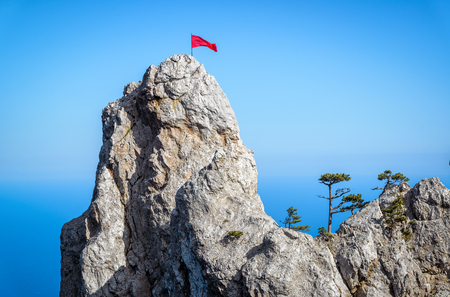 soviet flag: The rock on Mount Ai-Petri with a red flag and trees over Black Sea in Crimea, Russia. Ai-Petri is one of the highest mountains in Crimea and tourist attraction.
