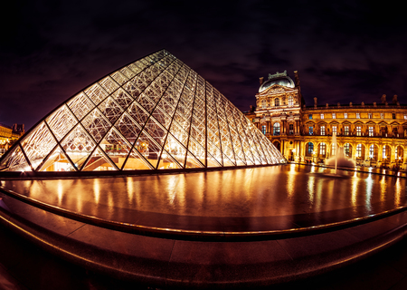 PARIS - SEPTEMBER 25, 2013: The famous glass pyramid at the Louvre. The Louvre is one of the largest museums in the world and one of the major tourist attractions of Paris.