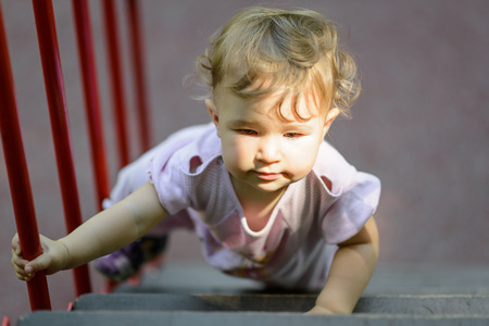 The one-year child climbs up the stairs. Cute baby girl plays on the playground.
