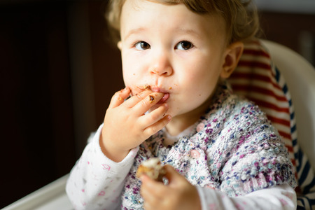 Eating baby girl with messy face. The one-year child eats and puts fingers in his mouth.