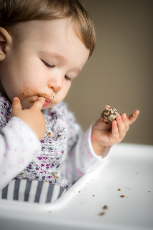 Eating baby girl with messy face. The one-year child eats cake and puts fingers in his mouth.
