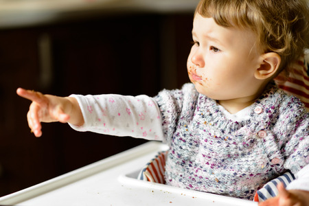 Eating baby girl with messy face and full mouth of food. The one-year child points his finger, demanding more food.