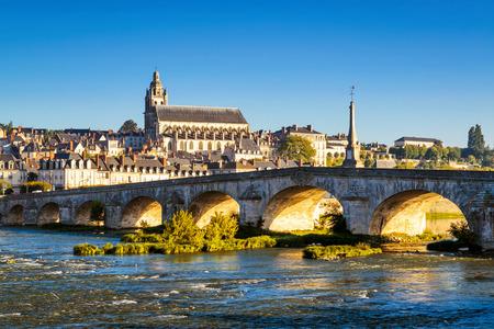 Ancien pont sur la Loire au coucher du soleil à Blois, en France. Cathédrale de Blois en arrière-plan. Banque d'images - 73349389