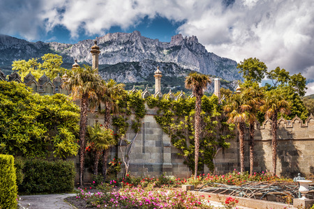 ALUPKA, CRIMEA - MAY 20, 2016: The garden in the Vorontsov Palace. Mountain Ai-Petri in the distance. This palace is one of the attractions of Crimea.
