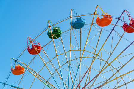 A colourful ferris wheel on the background of blue sky
